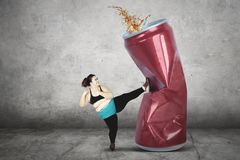 Obese woman kicking soft drink. Diet concept. Obese young woman kicking a can of soft drink while wearing sportswear Stock Photography