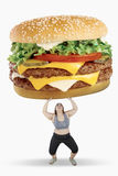 Obese woman lifting big hamburger. Picture of obese woman lifting big hamburger while standing in studio, isolated on white background Stock Image