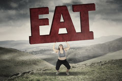 Obese woman lifting fat word in hills. Picture of obese woman lifting a big fat word while standing in hills Royalty Free Stock Photos