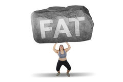 Obese woman lifting stone with fat word. Obese woman lifting a big stone with fat word while standing in studio, isolated on white background Royalty Free Stock Images