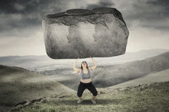 Obese woman lifting stone in hills. Picture of obese woman lifting a big stone while standing in hills Stock Images
