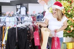 Obese woman looking into her Christmas gifts. Image of obese woman looking into her shopping bags after buying Christmas gifts in the department store Stock Photo