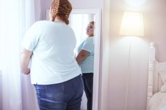 Obese woman looking at herself in the mirror. Mirror on the wall. Stout young woman standing next to mirror while admiring herself Royalty Free Stock Images
