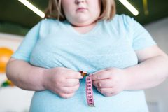 Obese Woman Measuring Waist. Mid-section portrait of young obese woman measuring waist size with tape measure after fitness training in gym royalty free stock image