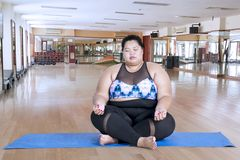 Obese woman meditating in the fitness center stock image
