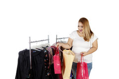 Obese woman with paper bag and clothes. Happy obese woman looking at her shopping bags with clothes hanger on the background Royalty Free Stock Image