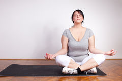 Obese woman practising yoga Royalty Free Stock Photo