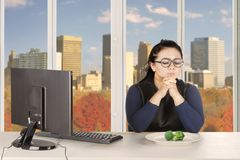 Obese woman prays with broccoli on plate Stock Image