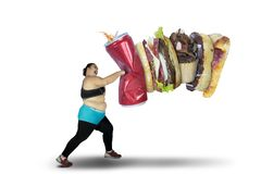 Obese woman punching unhealthy food. While wearing sportswear,  on white background Royalty Free Stock Images