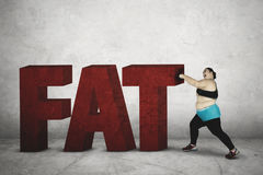Obese woman punching word of fat Royalty Free Stock Photography