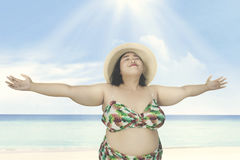 Obese woman relaxing on beach. Obese woman wearing straw hat, relaxing on the beach Royalty Free Stock Photography