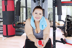Obese woman resting on gym equipment Stock Image