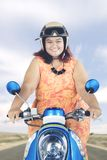 Obese woman riding a motorcycle on the highway. Portrait of obese woman looks happy while riding a motorcycle on the highway Stock Image