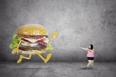 Obese woman running away from a hamburger. Picture of obese woman is running away from a hamburger. Concept of diet Royalty Free Stock Images