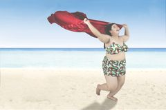 Obese woman with scarf runs on beach. Joyful obese woman wearing bikini and running on the beach while holding a red scarf Royalty Free Stock Photography