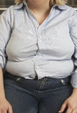Obese Woman Sitting. Midsection of an obese woman in casual wear Stock Photo