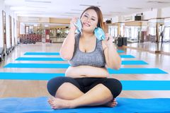 Obese woman sitting on the mat. Image of obese woman wiping her sweat after doing a workout while sitting on the mat Stock Images