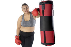Obese woman standing and boxing bag. Portrait of a young overweight woman standing next to boxing bag while wearing sportswear and boxing gloves Stock Images