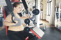 Obese woman is training with weight machine. Obese woman wearing sportswear while training her bicep with weight machine in the fitness dream Royalty Free Stock Photography