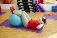 Obese Woman Working Out Using Fitness Ball in Gym. Side view  portrait of young obese woman working out in gym: using fitness ball for sit ups  with effort to Stock Images