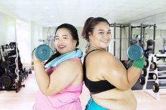 Obese women doing exercise together. Two obese women wearing sportswear and doing exercise together with dumbbells in the fitness center stock photos