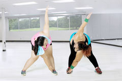 Obese women doing stretching at gym. Two obese women doing stretching together at the gym while wearing sportswear Stock Images