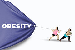 Obese women pull Obesity word Royalty Free Stock Photo