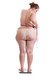 Obese women on scales measuring waist size Royalty Free Stock Photography