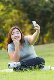 Obese women selfie. Beautiful obese woman sitting on grass and taking selfie Stock Photos
