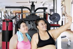Obese women with smartphone in gym center. Two obese women taking a selfie photo with a smartphone after workout in the gym center Stock Image