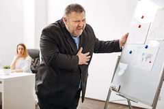 Obese worker feeling extreme pain in the chest royalty free stock images