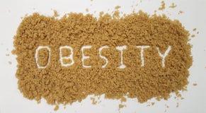Obesidad deletreada hacia fuera en el azúcar de Brown en el fondo blanco fotografía de archivo