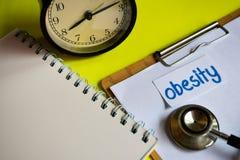 Obesidad en la inspiración del concepto de la atención sanitaria en fondo amarillo imagenes de archivo