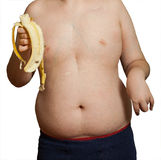 Obesity. The body of the boy's disease and metabolic disorders.Child obesity holds peeled banana in hand royalty free stock photo