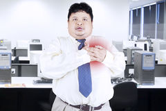 Obesity businessman getting heart attack Royalty Free Stock Image