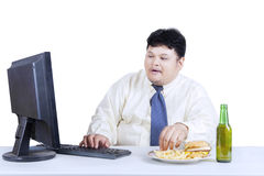 Obesity businessman working while eating Stock Photo