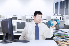 Obesity businessman working while workout Royalty Free Stock Image