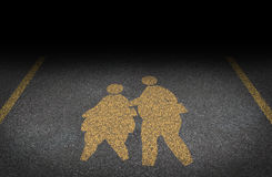 Obesity In Children. And childhood obese concept with a yellow painted asphalt road sign showing an icon of overweight kids and young students as a warning to Royalty Free Stock Photo