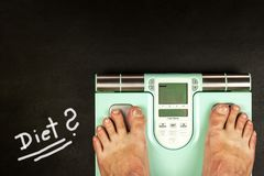Obesity concept. Modern digital weight and legs. Weight control on diet.  royalty free stock photography