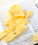Obesity dictionary. Obesity illustrated with potatoe chips on dictionary Stock Image