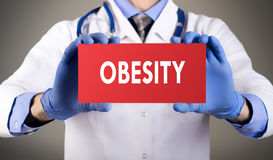 Obesity. Doctor`s hands in blue gloves shows the word obesity. Medical concept Royalty Free Stock Photography