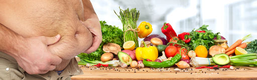 Obesity and healthy food. Fat man with big belly over vegetables background Royalty Free Stock Photography