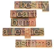 Obesity, heartburn, allergies and asthma. Health problems - obesity, heartburn, allergies and asthma -isolated words in vintage wood letterpress printing blocks stock image