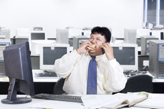 Obesity manager eat while working. Overweight businessman working in the office while eating burger and calling with mobilephone Stock Photos