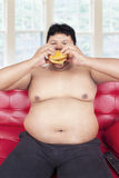 Obesity person eating burger on sofa Stock Photo