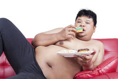 Obesity person eating donuts on sofa. Lazy fat person eating donuts while sitting on the sofa, isolated on white background Stock Photography