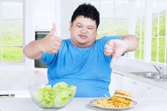 Obesity person with salad and burger Royalty Free Stock Images