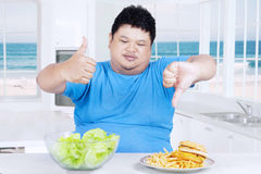 Obesity person with salad and fast food. Overweight Asian person showing thumb up at the salad and thumb down at the burger in the kitchen Royalty Free Stock Photos