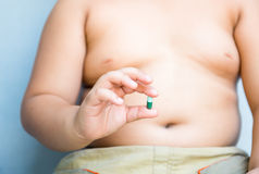Obesity pill in fat hand Stock Photo