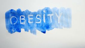Obesity text inscription watercolor artist paints blot isolated on white background art video. Obesity text inscription watercolor artist paints blot isolated on stock images